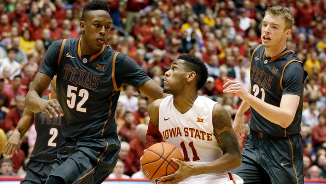 Iowa State guard Monte Morris, center, drives to the basket between Texas defenders Myles Turner, left, and Connor Lammert, right, during the first half of an NCAA college basketball game, Monday, Jan. 26, 2015, in Ames, Iowa. (AP Photo/Charlie Neibergall)
