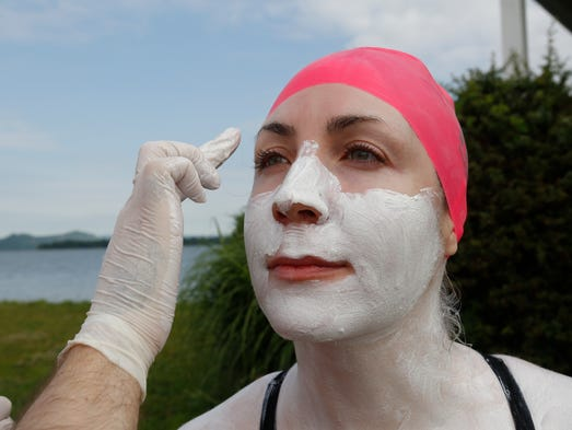 Arik Thormahlen puts on zinc oxide on Jaime Monhan before the start of the 8 Bridges Hudson Valley Swim stage 6 swim between the Tappan Zee Bridge and the George Washington Bridge on June 24, 2014.