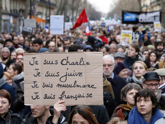 "A woman holds a cardboard reading, in French, ""I am Charlie, I am Jewish, I am a Muslim, I am French,"" during a Unity rally Marche Republicaine in Paris on Jan. 11, in tribute to the 17 victims of a three-day killing spree by homegrown Islamists."