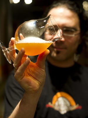 Irondequoit native Evan Lewis inspects one of his creations. He started Aegir Brewery in 2007 in Flam, Norway.