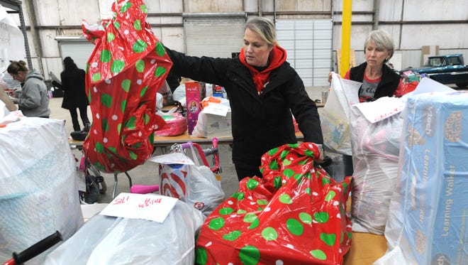 """Volunteers Teri Dillon, left, and Donna Watkins organize Christmas gift donations collected by the Taylor County Child Welfare Board to serve 290 abused or neglected children in their program.  The """"Miracle on Vine Street,"""" the board's annual toy drive, pairs children in CPS care with community donors who buy the gifts. Each child received several gifts, based on a form they filled out about things they need, want and would like to read."""