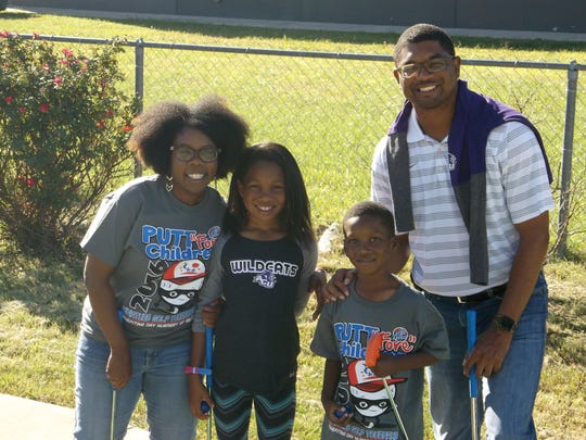 Day Nursery of Abilene board chair CaSaundra Johnson and her family participate in the Putt �Fore� Children Miniature Golf Tournament.