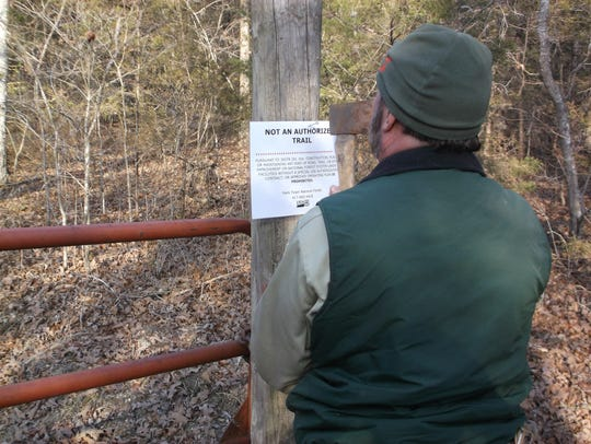 A U.S. Forest Service employee posts a sign declaring