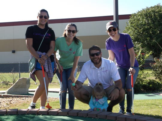 The Care Options Team plays in the ninth annual Putt Fore Children Miniature Golf Tournament.