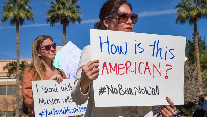 LaDawn Haglund, an ASU faculty member, left, and Leila Asadi, an ASU student from Iran, hold up signs on campus during the protest against the visa and immigration bans recently enacted.  The protest was part of a nationwide event called Academics United-No to Visa and Immigration Ban in solidarity with International Academics.