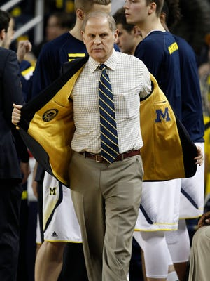 Michigan basketball coach John Beilein takes off his jacket at the start of a game against Iowa on Feb. 5, 2015, in Ann Arbor.