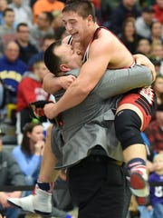 William Penn wrestling coach Marvin Dooley bear hugs his son, Brandon, after the younger Dooley on the 285-pound title at the 2015 DIAA Individual Wrestling Championships at Cape Henlopen High.
