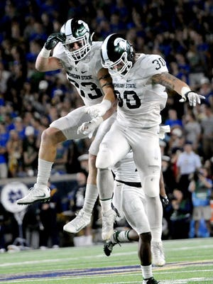 Michigan State University junior linebacker Jon Reschke (33) and Michigan State University senior linebacker Riley Bullough (30) jump into eachother to celebrate Reschke's interception in the second half of the Spartans game against Notre Dame Saturday, Sept. 17, 2016 in South Bend, Ind. He finished the game with eight tackles and an interception in the Spartans 36-28 win.