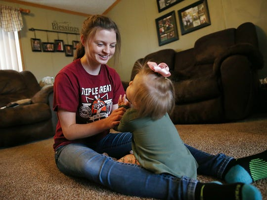 Felicity Graf, 17, plays with her sister Jayklin Graf, 1, at their home in Bloomfield, Ind., Wednesday, Jan. 25, 2017. Graf, a senior basketball player at Bloomfield, has six siblings who she helps care for while her parents are in Indianapolis with Jayklin, who receives treatment for Rubinstein-Taybi syndrome at Riley Hospital for Children.