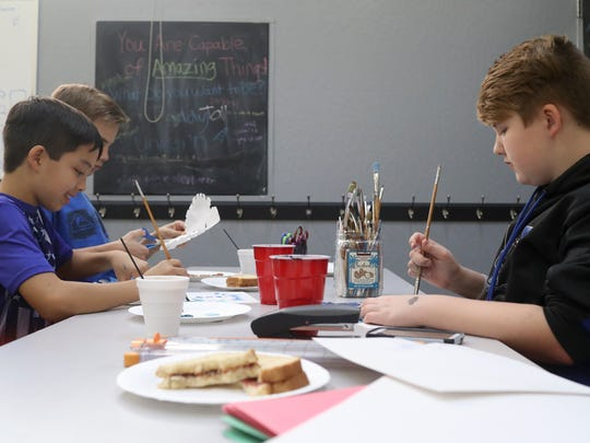 Nathan Chow, 11, from left, Jack Hamilton, 12, and Caden Gregory, 12, work on arts and crafts Tuesday during YCLUB at the Shasta Family YMCA.