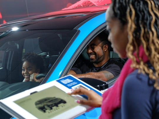 Tim Dawkins, 32, of Detroit sits in a 2018 Ford Focus RS Hatch with Alayna Jackson, 8, of Detroit as her mother Dyana Curtis of Detroit looks over information about the car at the Ford section during the 2018 North American International Auto Show at Cobo Center in downtown Detroit on Monday January 22, 2018.