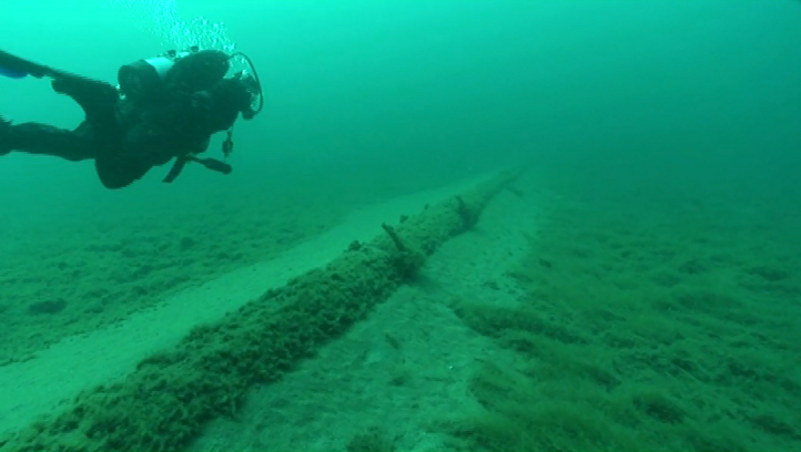 A diver working on behalf of the nonprofit National Wildlife Federation inspects the Line 5 oil pipelines at the lake bottom in the Straits of Mackinac during a July 2013 dive.