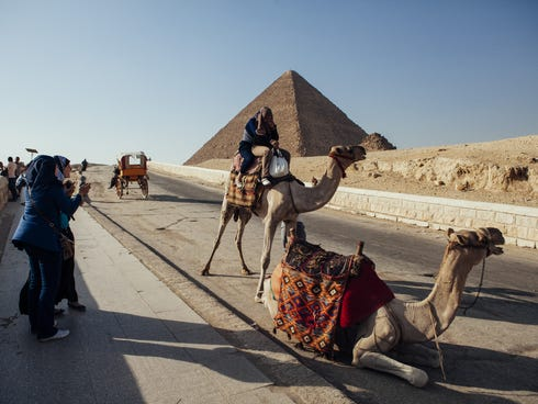 A tourist rides a camel at the Pyramids of Giza compound as friends look on. After a summer of violence, tourist numbers across Egypt are at their lowest levels since a 2010 peak in tourism in the country.