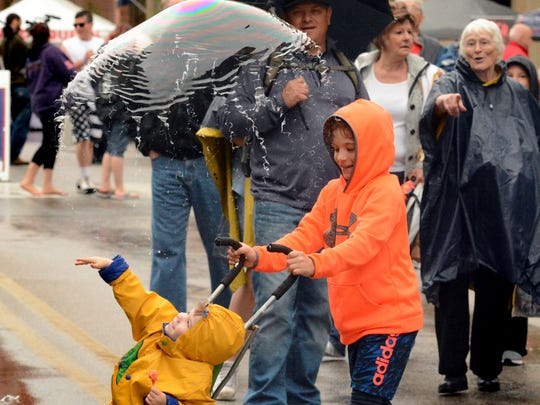 Bodie Barley, 2, of Spring Garden Township, bursts a bubble lofted by Bubbletopia while being pushed by his brother James, 7, during the 43rd Annual Olde York Street Fair on Sunday, May 13, 2018. Bubbletopia sells an assortment of bubble-making goods. The fair is a Mother's Day tradition in York. Bill Kalina photo