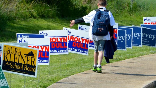 A student tags each campaign sign lining the walkway as he heads home from Bessie Weller Elementary School which also served as the Ward 1 polling place in Staunton on Tuesday, May 6, 2014.