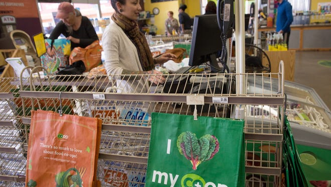 Re-Useable bags hang near the cash registers at Mountain View Market Co-op as Nags Suzuki, the store manager at Mountain View Market Co-op, bags groceries in a reusable bag for Geri Murphy, a customer and member of the Co-op, Tuesday, January 10, 2017.