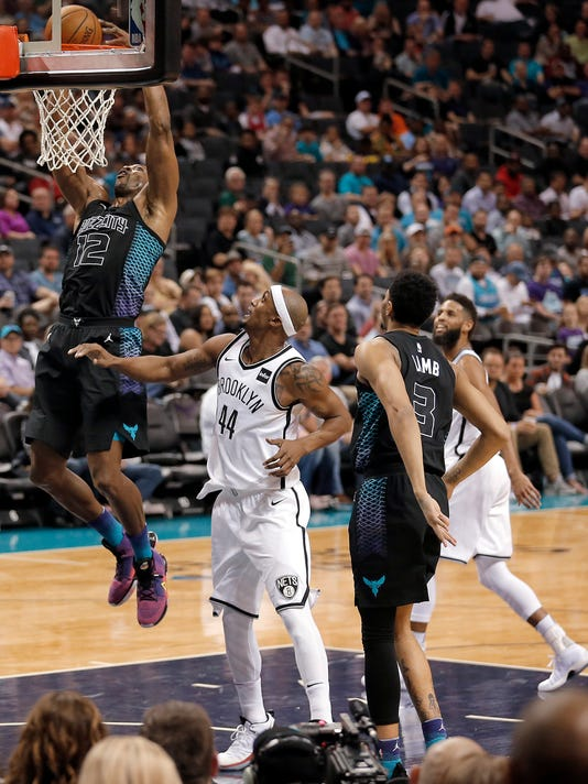 Charlotte Hornets' Dwight Howard (12) dunks as Brooklyn Nets' Dante Cunningham (44) watches during the first half of an NBA basketball game in Charlotte, N.C., Thursday, Feb. 22, 2018. (AP Photo/Bob Leverone)