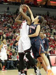 University of Louisville's Sara Hammond (12) fights to get her shot off under pressure from University of Virginia's Sarah Beth Barnette (3) during the first half of play at the KFC Yum! Center in Louisville, Kentucky.      January 18 , 201