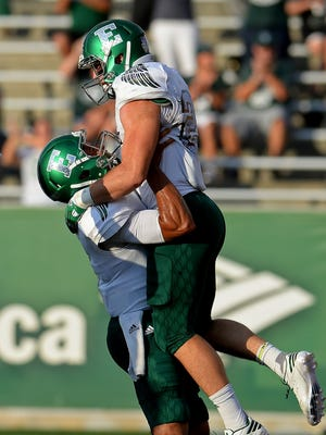 Eastern Michigan's Ian Eriksen, right, is lifted into the air by quarterback Todd Porter, left, after Eriksen rushed 5 yards for a touchdown run against Charlotte in the first quarter on Saturday, Sept. 17, 2016, at Richardson Stadium in Charlotte, N.C.