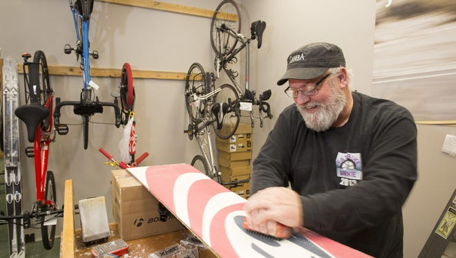 Sheboygan Bicycle Company owner Dan Dittrich waxes a snowboard Thursday February 22, 2018 at his new Taylor Heights location.  Dittrich, who moved from a location at the Sheboygan Riverfront, said the new location at 537 S. Taylor Drive at Taylor Heights puts him close to the The Old Plank Road Trail.