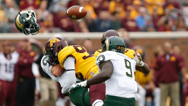 Colorado State quarterback Collin Hill loses his helmet after being tackled by Minnesota defensive lineman Tai'yon Devers.