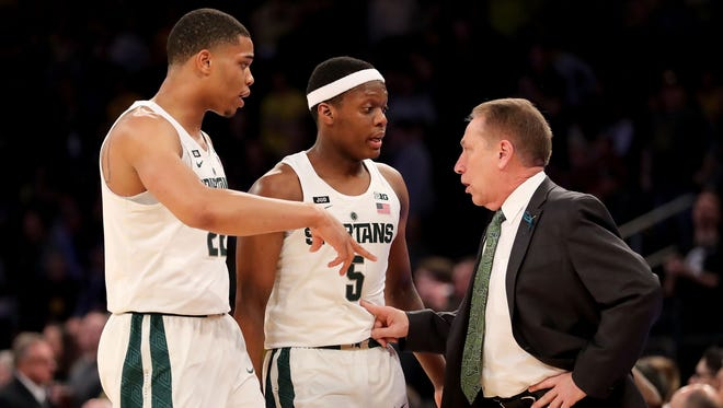 Miles Bridges #22 (L), Cassius Winston #5 and head coach Tom Izzo of the Michigan State Spartans have a conversation in the first half during semifinals of the Big 10 Basketball Tournament at Madison Square Garden on March 3, 2018 in New York City.
