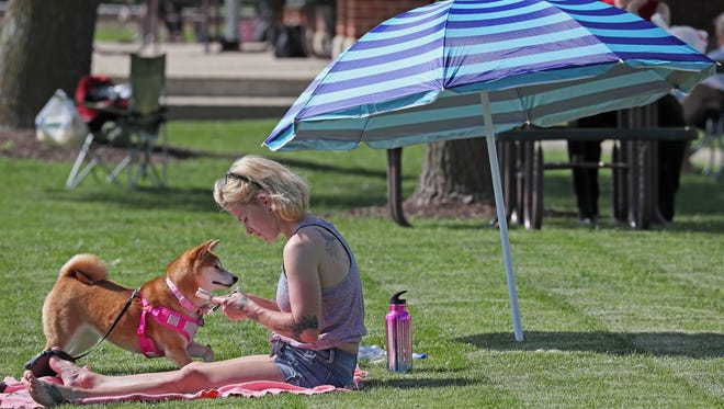 Chrystle Betts of Pewaukee and her dog, Nala, relax on the grass at Lakefront Park. Oconomowoc recently approved an amendment to allow dogs in some city parks.
