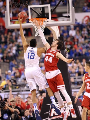 Kentucky Wildcats forward Karl-Anthony Towns (12) goes for the basket as Wisconsin Badgers forward Frank Kaminsky (44) tries to block in the first half of the 2015 NCAA Final Four semi finals game of Wisconsin versus Kentucky Saturday, April 4, 2015 at Lucas Oil Stadium.
