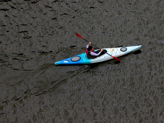 A person maneuvers a kayak just south of the E. Juneau Ave. bridge on the Milwaukee River in Milwaukee.