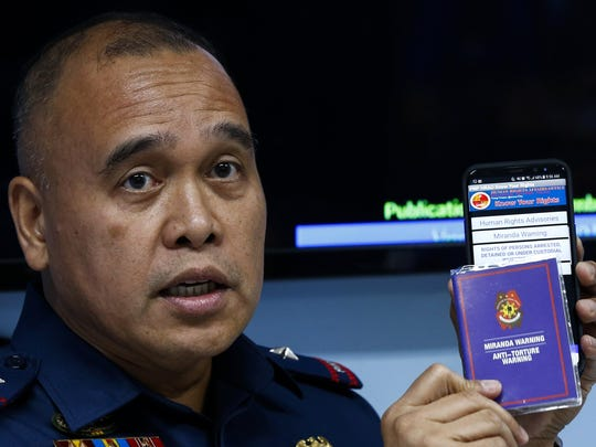 Police Chief Superintendent Dennis Siervo, Chief of the Philippine National Police (PNP) Human Rights Affairs Office, shows a Miranda Warning (Miranda Rights) booklet and a smartphone application containing information on human rights and police procedures during a press conference in Quezon City, east of Manila, Philippines, Dec. 4 2017. The PNP launched an application for android smartphones called 'Know Your Rights', aimed at guiding police officers in conducting operations and providing citizens with information about their human rights when faced with issues of law enforcement.