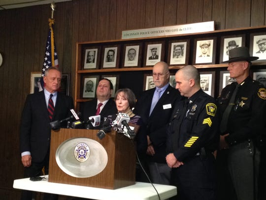 Cheryl Cole Candelaresi speaks at a podium Wednesday about the parole hearing next month for one of the men who in 1974 killed her husband, a Cincinnati police officer.