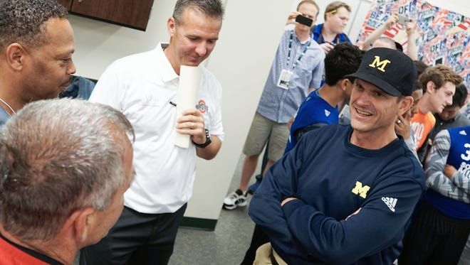 Michigan head coach Jim Harbaugh speaks with Ohio State coach Urban Meyer, center,  and other coaches at the Sound Mind Sound Body Football Camp on Friday, June 12, 2015 at Dakota High School in Macomb.