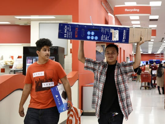 A Black Friday shopper carries his new television out