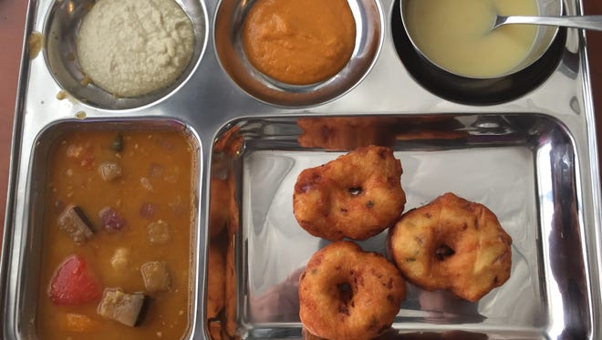 Fritters made from urad dal, or black gram beans, are served at Maya's South Indian Cuisine with tomato and coconut chutney.
