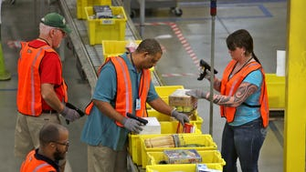 Workers get orders ready to pick at the Amazon Whitestown Fulfillment Center, Monday, December 1, 2014.  Cyber Monday is their busiest day.