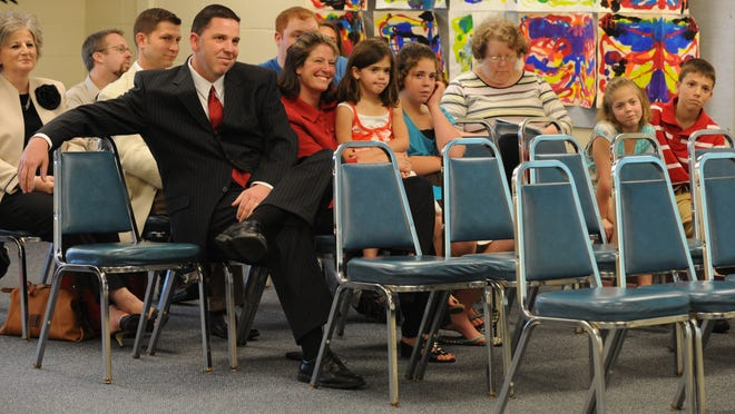 Joe Luce, wearing dark suit, sits with his family during the Richmond Community Schools board meeting on May 27, 2009, where he was accepted as the new Richmond High School boys varsity basketball coach.