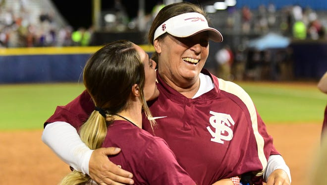 Florida State softball head coach Lonni Alameda and a volunteer for the coaching staff celebrate the Seminoles' first NCAA softball title.
