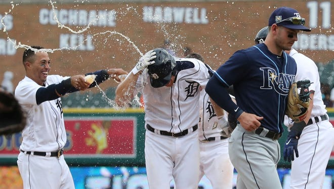 John Hicks is sprayed with water after he drove in the winning run with an RBI bunt single in the 12th inning on Wednesday.