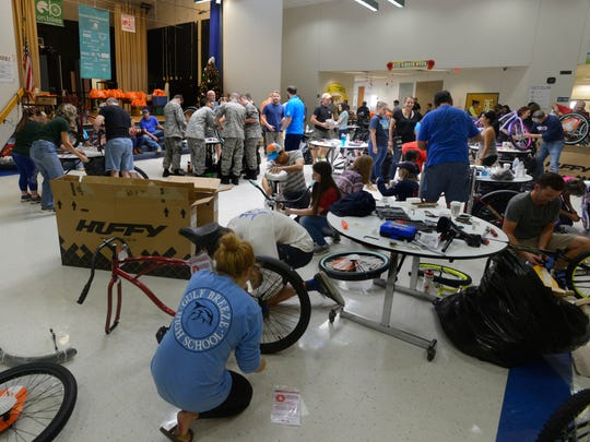 Volunteers help put together bikes on Saturday, Dec.