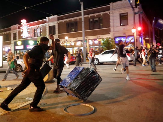 People overturn trash cans and throw objects as police