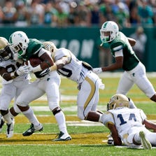 A Tulane runner is wrapped up by Georgia Tech defenders Saturday.