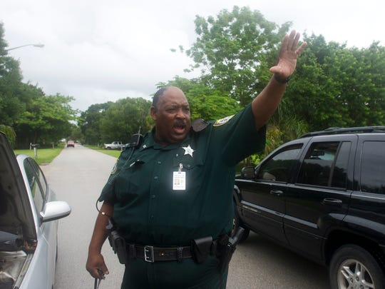 Indian River County Sheriff's deputy Teddy Floyd waves to Gifford residents as they prepare for Hurricane Matthew on Thursday, October 6, 2016.