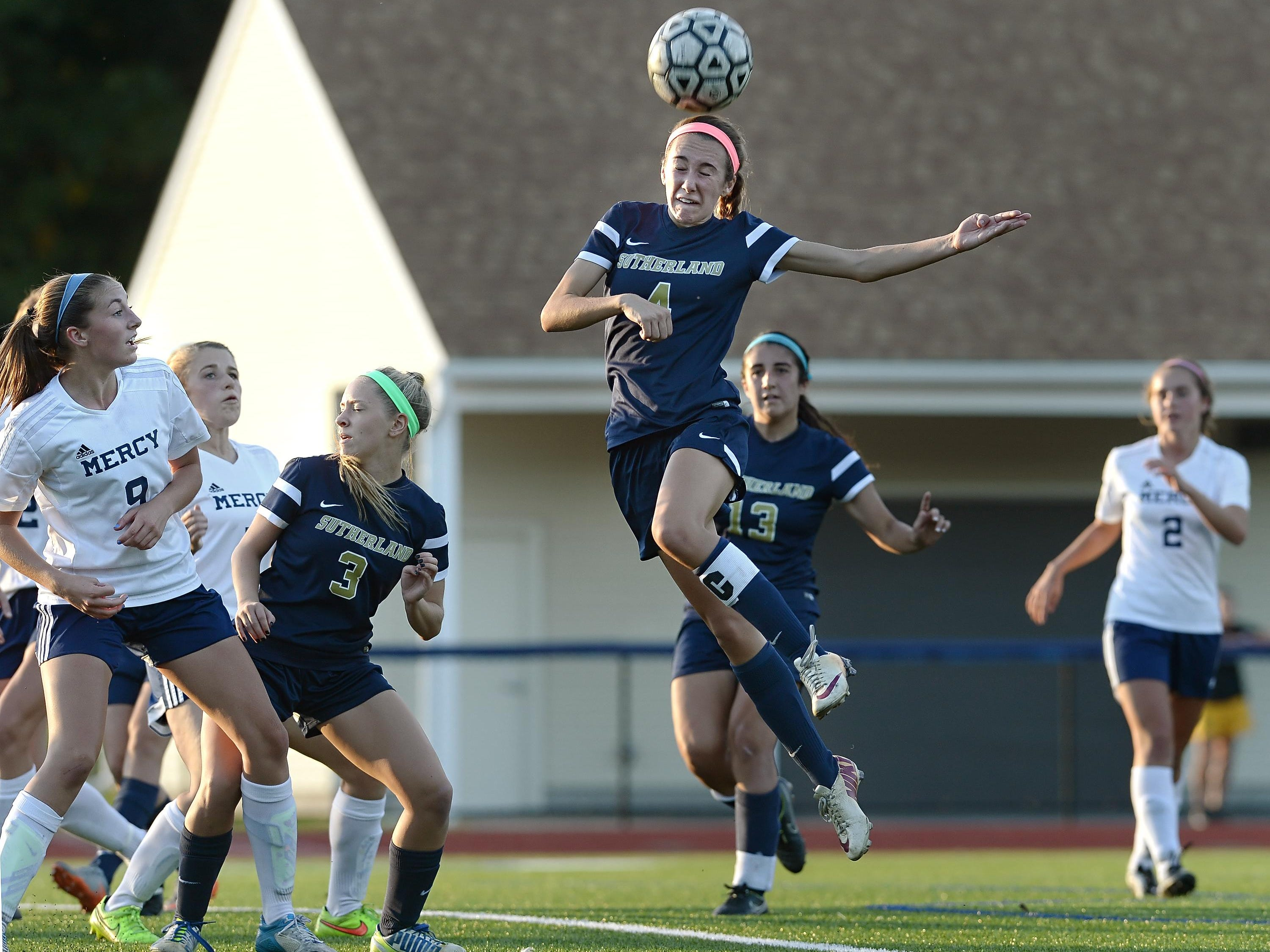 Pittsford Sutherland's Grace Dunnigan, center, reaches for a header on a corner kick.
