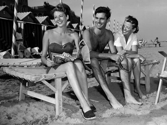 In this Set. 14, 1952, photo  actor Louis Jourdan sits with actress Anne Vernon, left, and his wife Berthe Fredrique on the beach at Lido isle in Venice, Italy.