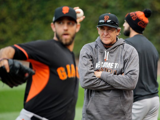 San Francisco Giants pitching coach Dave Righetti, right, watches as starting pitcher Madison Bumgarner warms up before Game 1 of baseball's National League Division Series against the Chicago Cubs, Friday, Oct. 7, 2016, in Chicago. (AP Photo/Charles Rex Arbogast)