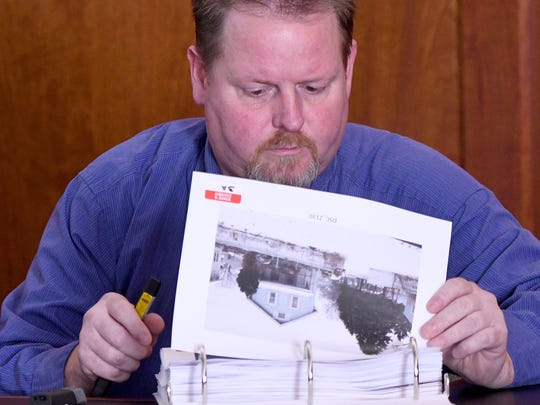 Lonnie Clevenger, son of Patsy Hudson, looks through exhibits while testifying in the Linda Buckner trial Thursday afternoon in Judge James DeWeese's courtroom.