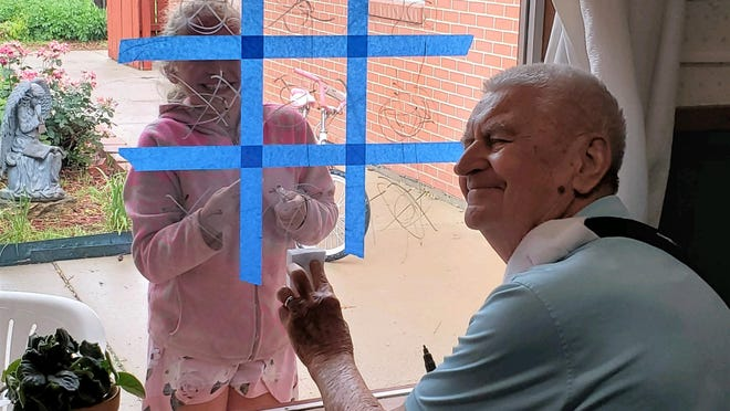 Bob Corbin, a resident at Bethany Home, plays tic-tac-toe through a window with Sydney, the daughter of a staff member.