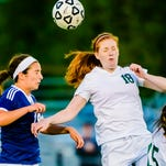 Victoria Surian ,left, of Haslett and Sydney Palmer of Williamston attempt to control the ball during their CAAC Gold Cup final game Thursday.