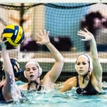 Carly Seeterlin (right) and teammate Sarah Williams (center) of Okemos look to lead the Chiefs back to the state finals.