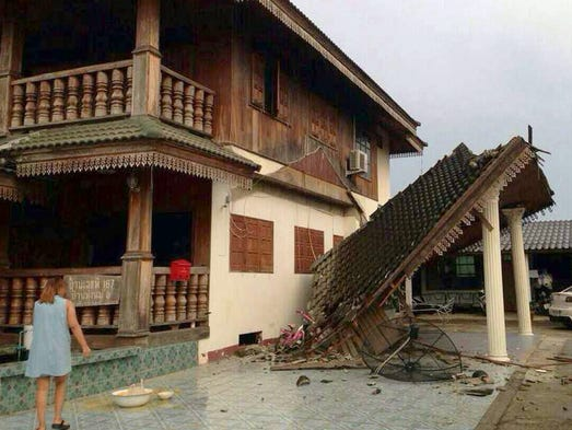 A woman looks at a damaged home following an earthquake on May 5 in Chiang Rai province, northern Thailand.  A strong 6.0-magnitude earthquake shook northern Thailand and Burma, causing minimal damage.
